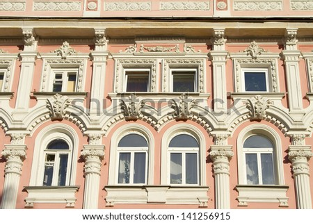 Stone facade of the building with plaster ornament