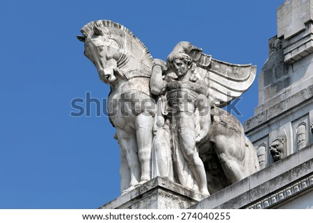 Stone facade of the Milan's main railway station, inaugurated in 1931 is topped with statues of winged horses.