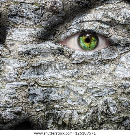 Stone face with green eye - stock photo