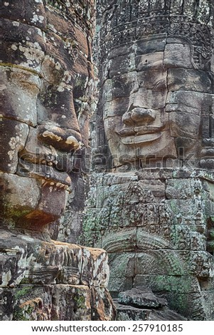 Stone faces of the Bayon, part of the temple complex of Angkor in western Cambodia. - stock photo