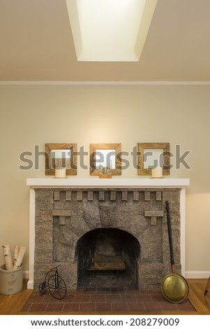Stone Fireplace in beige living room with skylight. - stock photo