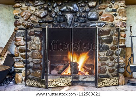 Stone fireplace in country house and fire blazing inside with natural light - stock photo