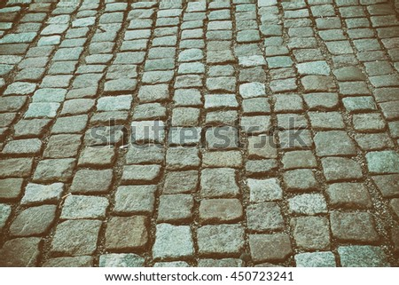 Stone floor background cobbles in an old European city, background and texture, with retro toning