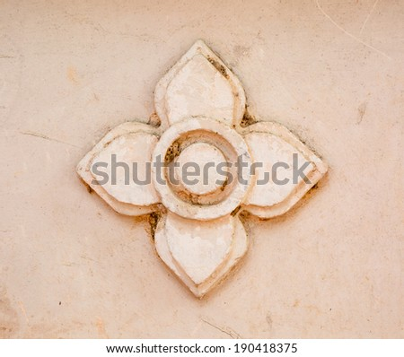 Stone flower on old cement wall - stock photo