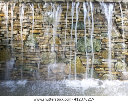 Stone fountain. Beautiful fountain over the colorful wall. - stock photo