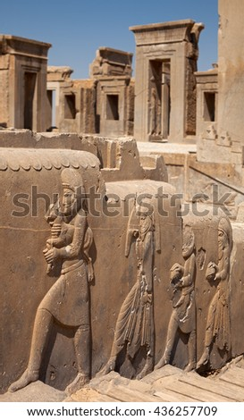 Stone frames of doorways to the palace of Darius behind embossed bas relief carvings of servants bringing gifts to the Achaemenian King at Persepolis of Shiraz. - stock photo