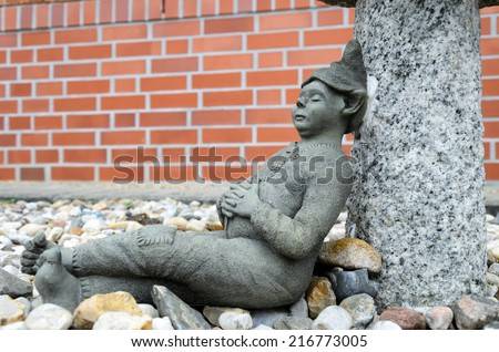 Stone garden gnome at the lunch break before the background of stones - stock photo