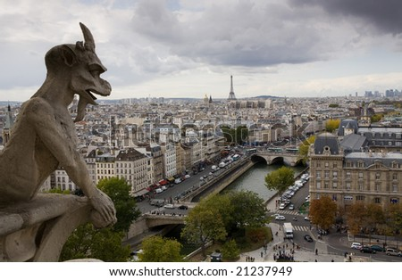 Stone gargoyle on top of Notre Dame Cathedral looking out to the city of Paris, France