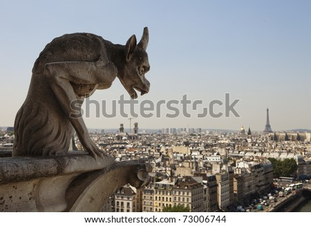 Stone gargoyle with horns peering over the city of Paris towards the Eiffel Tower while perched on a corner of the cathedral of Notre Dame. - stock photo