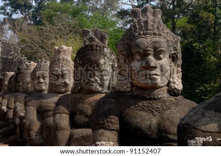Stone guardians of Angkor Wat gates 2 - stock photo