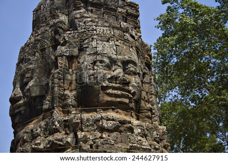 Stone heads which form part of the north gate at the entrance to Angkor Wat, a UNESCO World Heritage Site near Siem Reap, Cambodia. - stock photo
