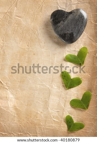 Stone Heart and little heart shaped leaves on old foxed paper - stock photo