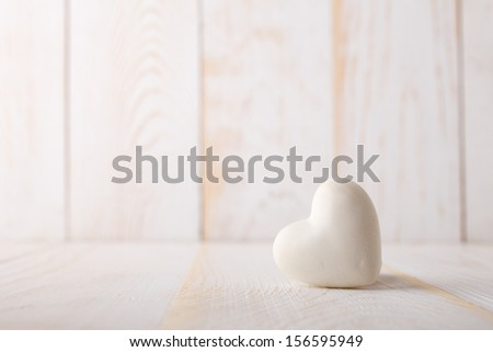 Stone heart on the white wooden background. - stock photo