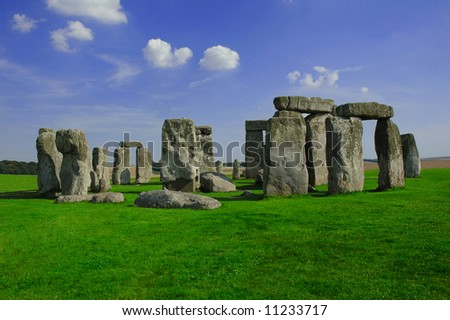 Stone henge with green grass and blue sky - stock photo