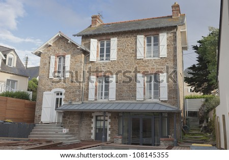 Stone house in Brittany with work on wooden terrace in progress - Saint-Malo, Brittany, France - stock photo