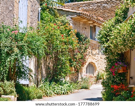 Stone houses among beautiful flowers in Provencal village. - stock photo