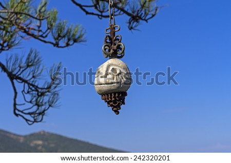 Stone idol, hanging on a pine tree in the Crimean mountains. Probably the temple of the followers of some new esoteric teaching. - stock photo
