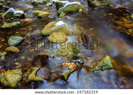 Stone in quick run of mountain brook at winter time - stock photo