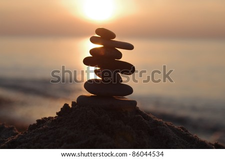 stone in  sand on sunset   background - stock photo