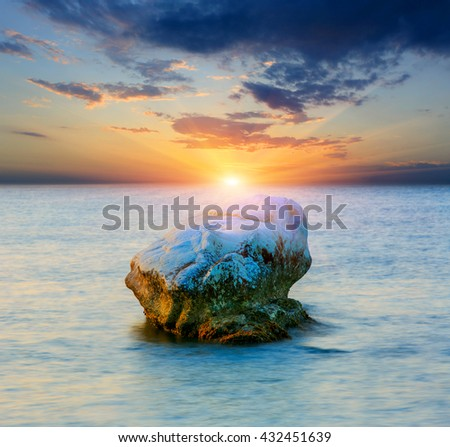 Stone in sea on sunset background