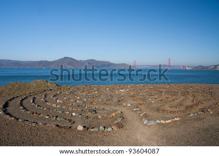 Stone labyrinth and Golden Gate Bridge seen from Coastal Trail in San Francisco - stock photo