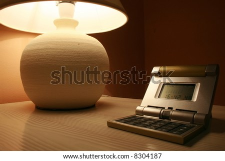 stone lamp and travel clock on a wooden cabinet - stock photo