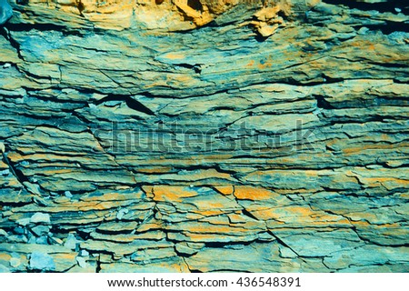 Stone layers of sedimentary rock resembling timber texture. Toned photo. - stock photo