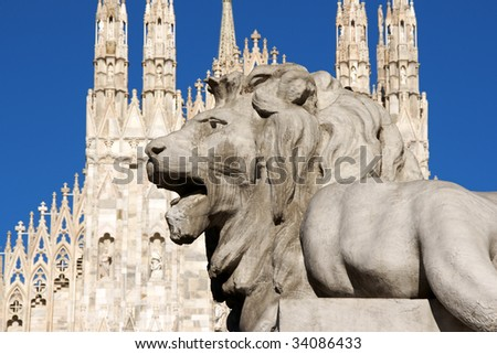 Stone lion from the basement of the monument to King Vittorio Emanuele the second in front of the gothic facade of Milan Cathedral in Piazza del Duomo. - stock photo
