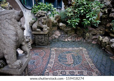 Stone Lion Statues And Floor Mosaic In YuYuan Garden In Shanghai, China