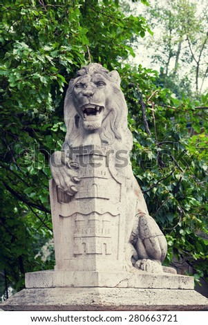 Stone lion with a board in paws near the Vajdahunyad castle in Budapest - stock photo