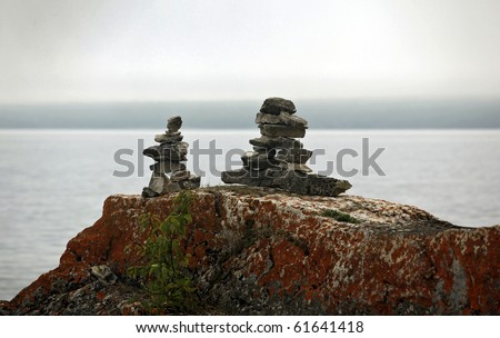 stone marker inukshuk on a lake shore - stock photo