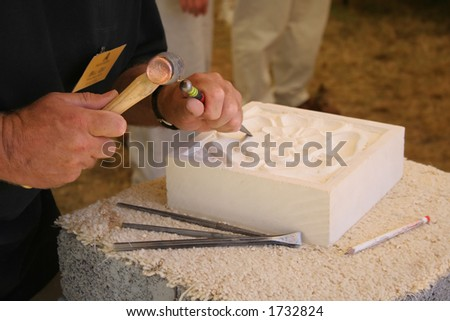 Stone mason at work carving an ornamental relief - stock photo