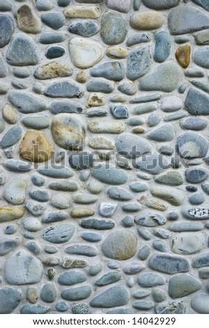 Stone masonry wall made with large rounded stones - stock photo