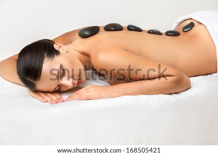 Stone Massage. Beautiful Woman Getting Spa Hot Stones Massage in Spa Salon.