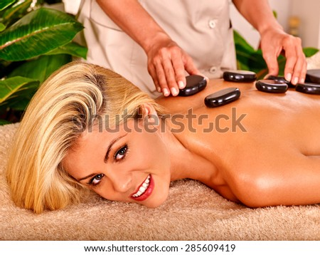 Stone massage of blond woman  in spa. - stock photo