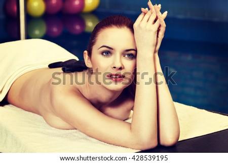 Stone massage, sensual woman getting a hot stone massage at spa salon. Instagram style. - stock photo
