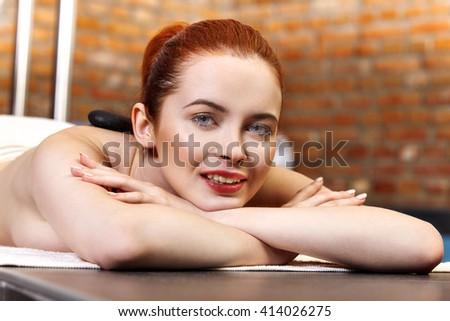 Stone massage, woman getting a hot stone massage at spa salon - stock photo