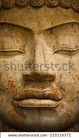 Stone old statue of a Buddha. Face close up