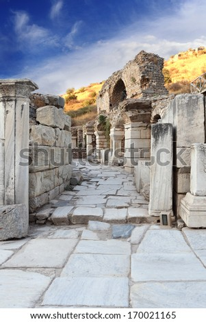 Stone passage in Ephesus with pillars and arches along the way - stock photo