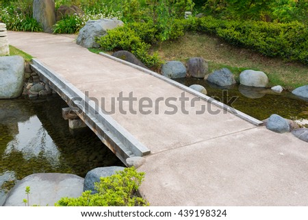 stone path in a japanese garden stone bridge across a tranquil pond - Japanese Garden Stone Bridge