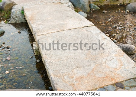 Stone path in a Japanese Garden, stone bridge, across a tranquil pond. - stock photo