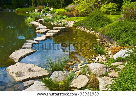 Stone path in a japanese water garden - stock photo