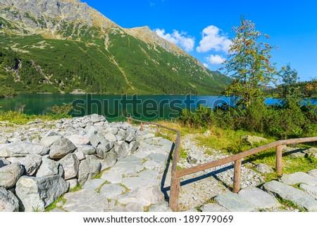 Stone path to Czarny Staw and green water mountain lake Morskie Oko below, Tatra Mountains, Poland - stock photo