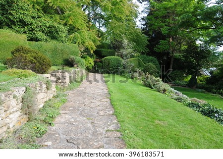 Stone Pathway and Lawn in a Peaceful Green Garden - stock photo