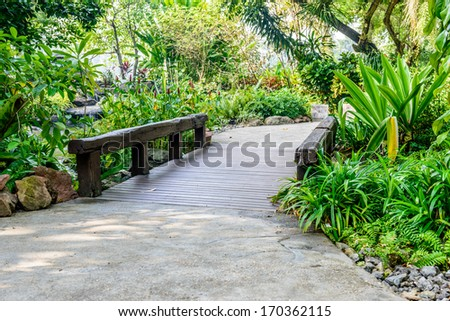 Stone pathway and wooden bridge into garden during day time - stock photo