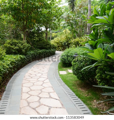 Stone pathway into garden during day time - stock photo