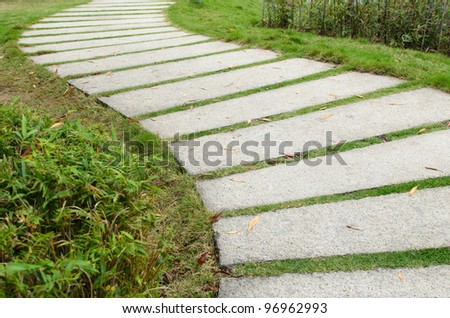 Stone pathway on grass - stock photo