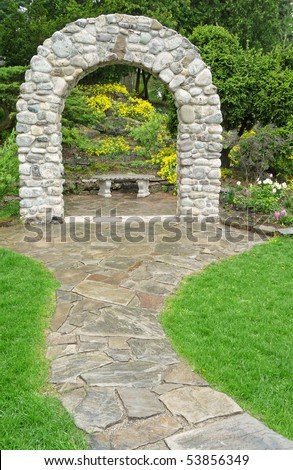 Stone pathway with arch and bench - stock photo