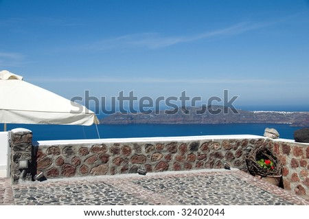stone patio view in imerovigli santorini of volcanic island  with classic whitewashed buildings over the caldera on the mediterranean sea greece - stock photo