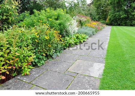 Stone Paved Path, Lawn and Flowerbed in a Peaceful English Garden - stock photo